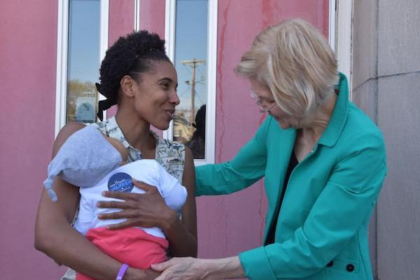Elizabeth Warren speaking to a mother and baby at the Brockton town hall