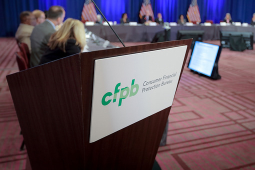"Podium with a sign on it that reads ""CFPB Consume Financial Protection Bureau"""