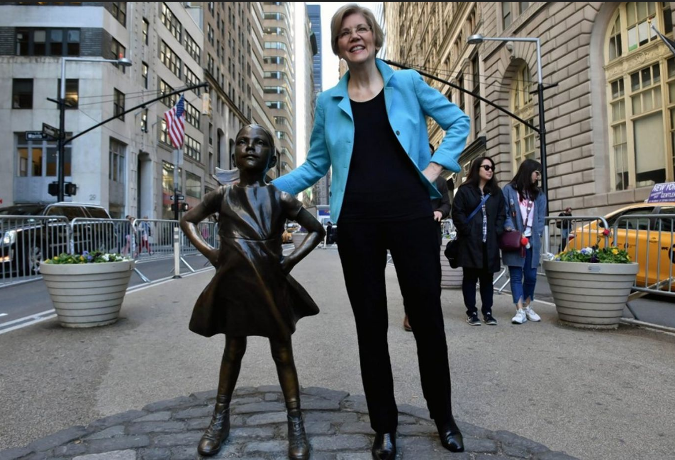 Elizabeth Warren standing with the Fearless Girl statue in Lower Manhattan