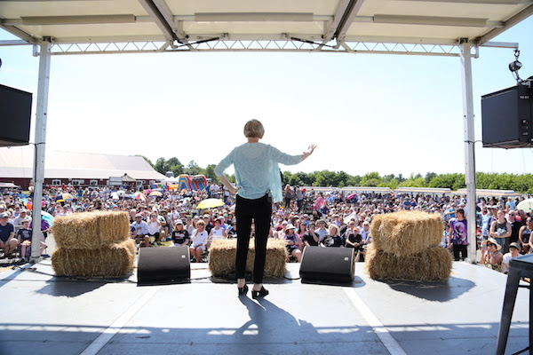 Elizabeth Warren standing on stage looking out at a town hall in Natick, MA
